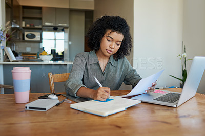Buy stock photo Shot of a young woman writing notes while going through paperwork at home