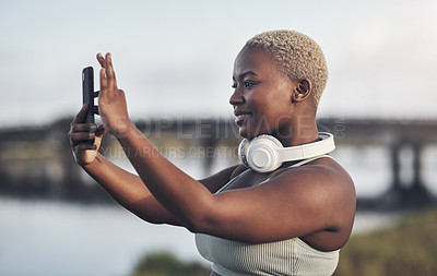 Buy stock photo Shot of a young woman taking pictures on her cellphone while out for a workout