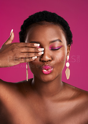 Buy stock photo Studio shot of a beautiful young woman covering her eye against a pink background