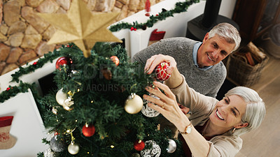 Buy stock photo Shot of a happy senior couple decorating their Christmas tree at home
