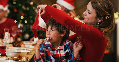 Buy stock photo Shot of a young woman putting her son's hat on during a Christmas dinner party at home