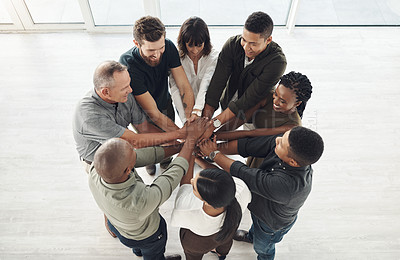 Buy stock photo Shot of a diverse group of businesspeople joining their hands together in a huddle