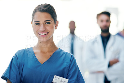 Buy stock photo Cropped portrait of an attractive young female nurse standing in the hospital with her colleagues in the background