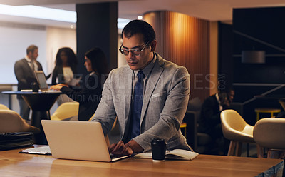 Buy stock photo Shot of a young businessman working on a laptop in an office at night