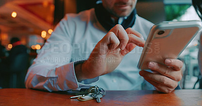Buy stock photo Man sitting at a table and looking into smartphone
