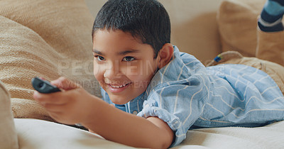 Buy stock photo Shot of an adorable little boy lounging on the sofa at home and watching tv
