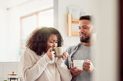 Buy stock photo Shot of a young couple enjoying a cup of coffee in their kitchen at home