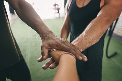 Buy stock photo Shot of three sporty young people joining their hands together in a huddle