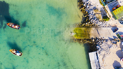 Buy stock photo Drone shot of boats anchored along the coastline of tranquil clear waters