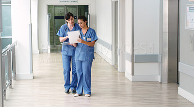 Buy stock photo Shot of two female doctors discussing medical documents at a hospital