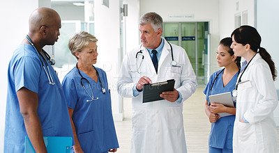 Buy stock photo Shot of a senior medical doctor discussing his notes with his diverse medical team in the hallway of the hospital