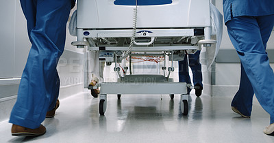 Buy stock photo Cropped shot of an unrecognizable medical team pushing a hospital bed in the hallway of the hospital
