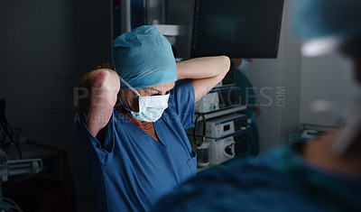Buy stock photo Shot of a female surgical nurse fastening her medical mask in the operating theatre