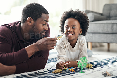 Buy stock photo Shot of a man and his young daughter playing with animal figurines at home