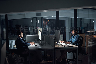 Buy stock photo Shot of young businessmen using their computers during a late night in a modern office
