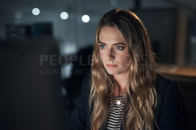 Buy stock photo Shot of a young businesswoman using a computer during a late night in a modern office