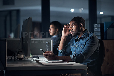 Buy stock photo Shot of a young businessman looking worried while using a computer during a late night at work