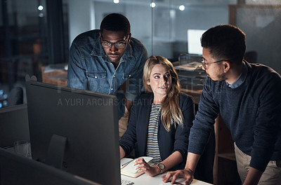 Buy stock photo Shot of a group of young businesspeople using a computer during a late night in a modern office
