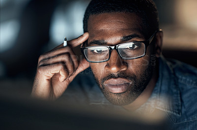 Buy stock photo Shot of a young businessman looking worried while using a computer during a late night in a modern office