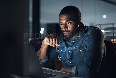 Buy stock photo Shot of a young businessman using a laptop during a late night in a modern office
