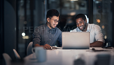 Buy stock photo Shot of two young businessmen using a laptop during a late night meeting in a modern office