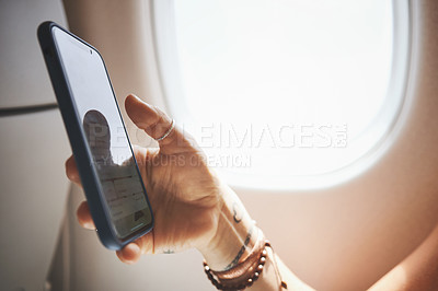 Buy stock photo Cropped shot of a woman using her phone in the aeroplane