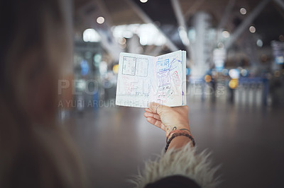 Buy stock photo Cropped shot of a woman showing her passport stamps at the airport