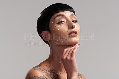 Buy stock photo Studio portrait of a beautiful young woman with pearls on her face posing against a grey background