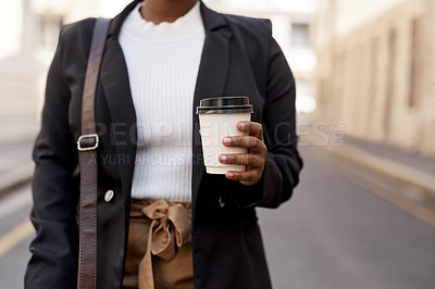 Buy stock photo Closeup shot of an unrecognisable businesswoman holding a coffee cup while out in the city