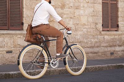 Buy stock photo Rearview shot of a young businessman riding a bike in the city