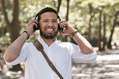 Buy stock photo Portrait of a young businessman wearing headphones outdoors