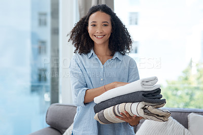 Buy stock photo Shot of a young woman holding a pile of clean folded laundry