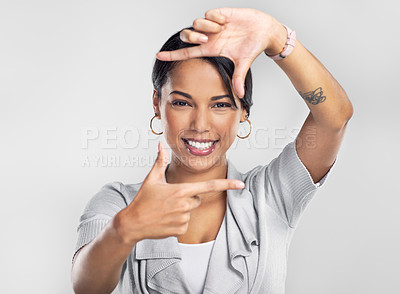 Buy stock photo Studio shot of a confident young businesswoman making a frame with her fingers against a grey background