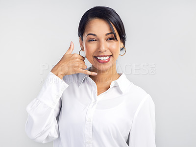 Buy stock photo Studio shot of a confident young businesswoman making a call me gesture against a grey background