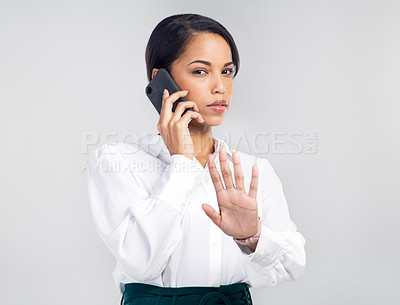 Buy stock photo Studio shot of a young businesswoman using a smartphone and gesturing to hold against a grey background