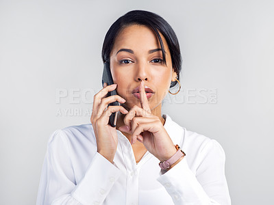 Buy stock photo Studio shot of a young businesswoman using a smartphone and placing her finger on her lips against a grey background