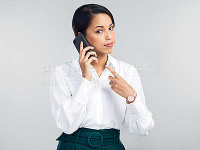 Buy stock photo Studio shot of a young businesswoman using a smartphone and pointing at her phone against a grey background