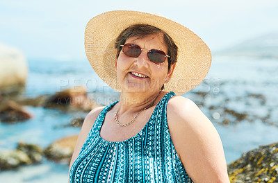 Buy stock photo Shot of an attractive mature woman standing alone during a day out on the beach