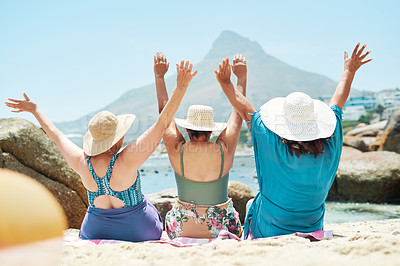 Buy stock photo Shot of an unrecognizable group of friends sitting together and raising her arms during a day on the beach