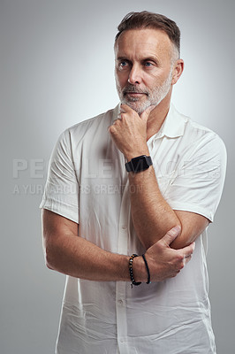 Buy stock photo Studio shot of a mature man looking thoughtful against a grey background