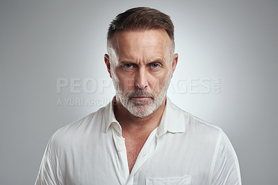 Buy stock photo Studio portrait of a mature man looking angry against a grey background