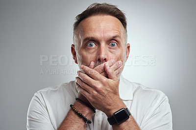 Buy stock photo Studio portrait of a mature man covering his mouth and looking shocked against a grey background