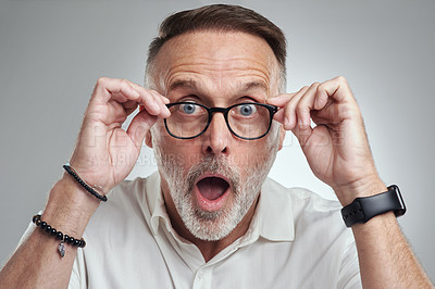 Buy stock photo Studio portrait of a mature man wearing spectacles and looking surprised against a grey background