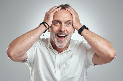 Buy stock photo Studio portrait of a mature man looking surprised against a grey background