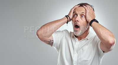 Buy stock photo Studio shot of a mature man looking surprised against a grey background