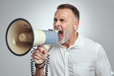 Buy stock photo Studio shot of a mature man using a megaphone against a grey background