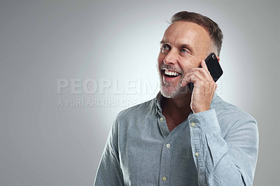 Buy stock photo Studio shot of a mature man talking on a cellphone against a grey background