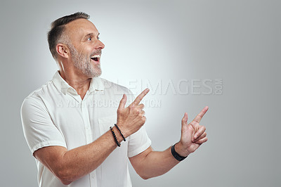 Buy stock photo Studio shot of a mature man pointing to copyspace against a grey background