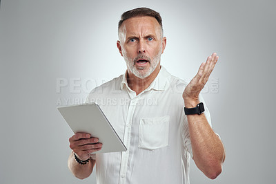 Buy stock photo Studio portrait of a mature man looking confused while using a digital tablet against a grey background
