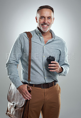Buy stock photo Studio portrait of a mature man carrying a bag and cup of coffee against a grey background